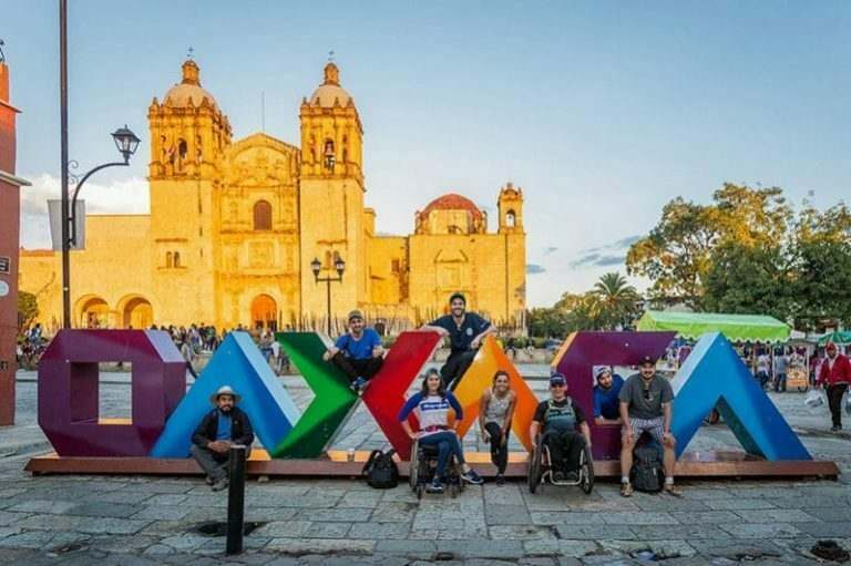 Disabled-english-teachers-in-oaxaca-with-a-multi-coloured-sign-and-a-church-in-the background