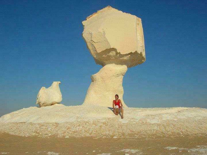 a-female-english-teacher-is-standing-in-the-farafra-oasis-in-egypt-next-to-a-natural-sand-sculpture